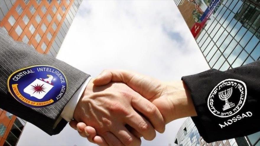 Logotipos de la CIA y el Mossad sobre las mangas de dos personas que se dan la mano.