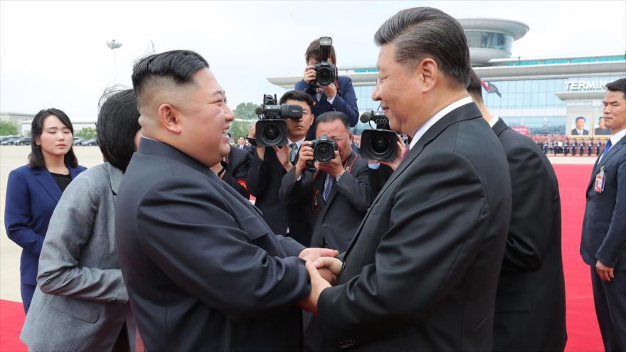 Xi Jinping (dcha.), presidente de China, y el líder de Corea del Norte, Kim Jong-un, se saludan en Pyongyang, 21 de junio de 2019. (Foto: AFP)