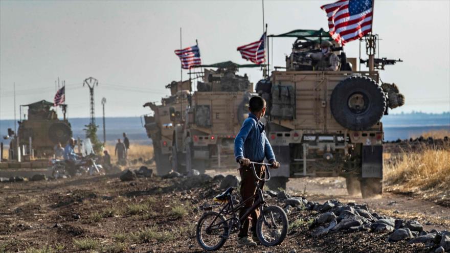 Un niño sirio en su bicicleta mira un convoy militar de EE.UU. cerca de la ciudad nororiental de Qahtaniyah, 31 de octubre de 2019. (Foto: AFP)