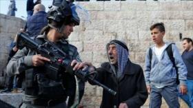 'Soldados israelíes apuntan con arma a palestino frente a su niño'