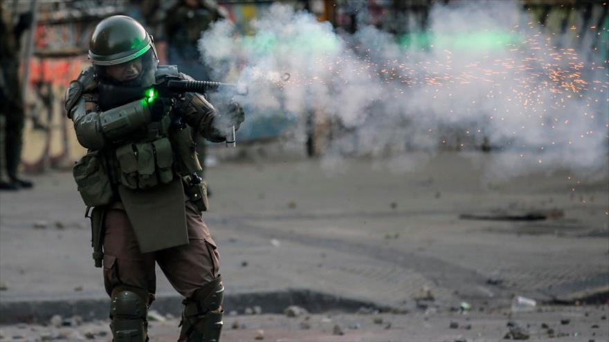 Un policía dispara contra manifestantes durante protestas en Santiago, la capital de Chile, 6 de noviembre de 2019. (Foto: AFP)
