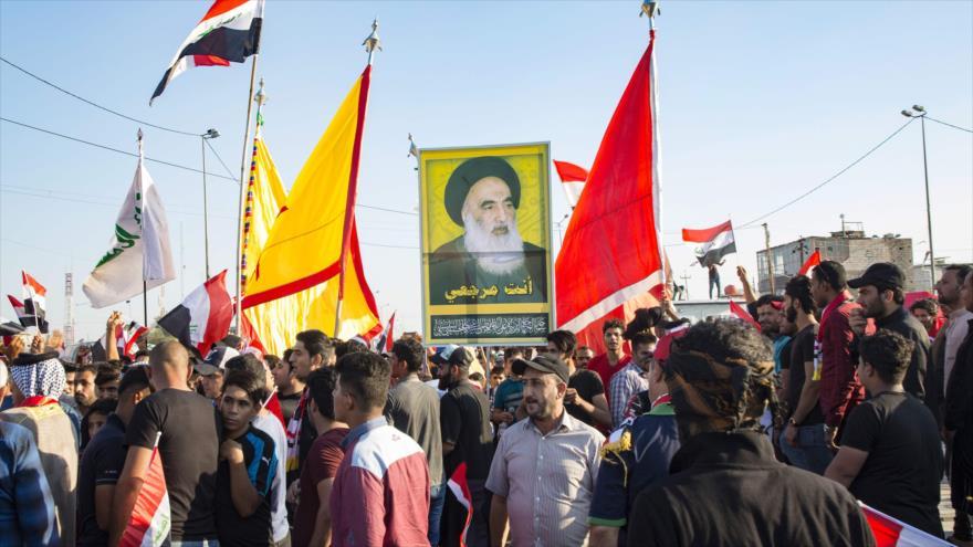 Manifestantes iraquíes llevan una imagen del máximo clérigo chií de Irak, el ayatolá Seyed Ali Sistani, en Basora (sur), 1 de noviembre de 2019. (Foto: AFP)