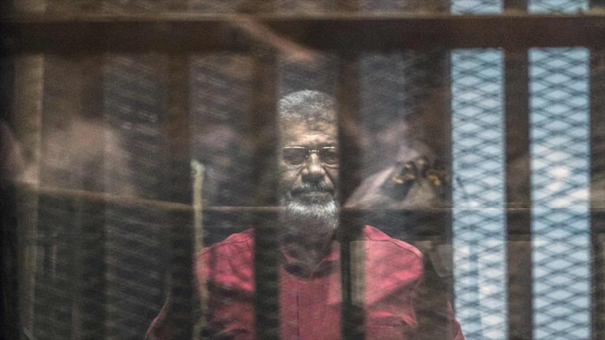 El fallecido expresidente de Egipto Muhamad Mursi en una sesión del juicio en su contra en El Cairo, capital egipcia, 23 de abril de 2016.