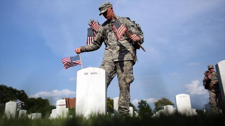 Un soldado estadounidense coloca la bandera de su país en las tumbas de sus compañeros difuntos.