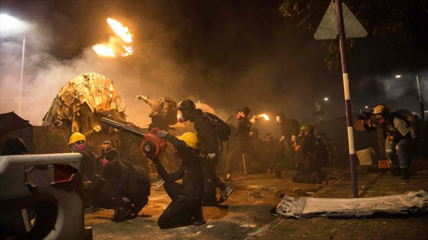 Unos manifestantes prenden fuego en protestas violentas en Hong Kong, 12 de noviembre de 2019. (Foto: AFP)