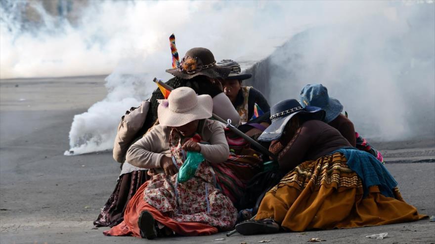 Mujeres indígenas bolivianas se protegen de los gases lacrimógenos durante una protesta contra el gobierno de facto, en La Paz, 15 de noviembre de 2019. (Foto: AFP)