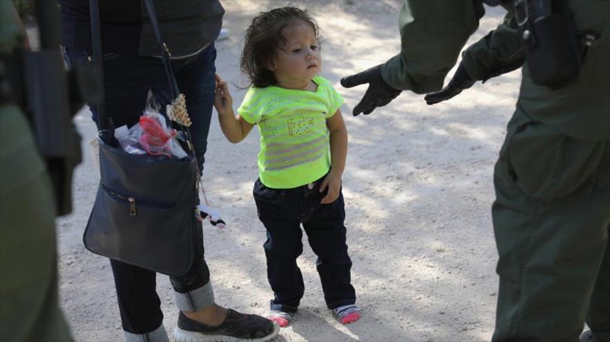 Una guardia fronteriza estadounidense intenta separa una niña de su madre.