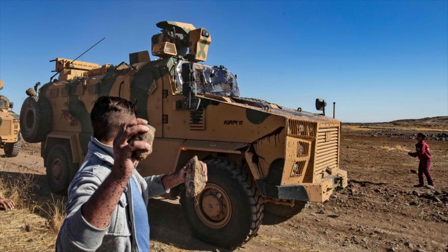 Manifestantes kurdos arrojan piedras contra un vehículo militar turco en el noreste de Siria, 8 de noviembre de 2019. (Foto: AFP)