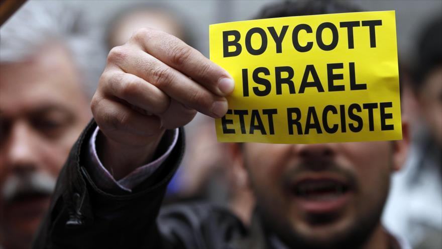"""Un manifestante belga muestra un cartel que pide boicot contra el régimen """"racista"""" de Israel. (Foto: Reuters)"""