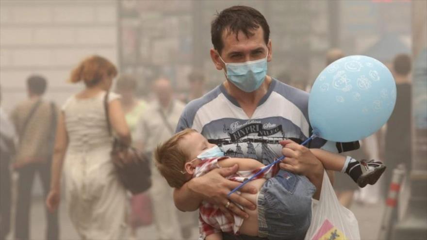 Unas personas usan máscaras para protegerse de la contamination del aire.