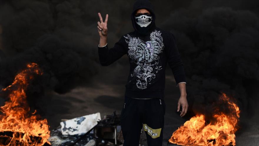 Un supuesto manifestante iraquí en medio de fuego prendido durante las protestas en la ciudad sagrada de Nayaf, 27 de noviembre de 2019. (Foto: AFP)