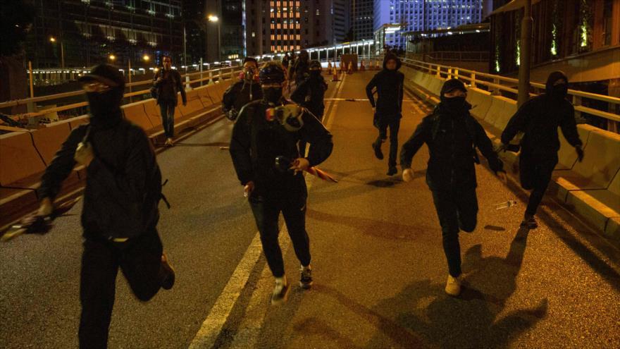 Varios manifestantes huyen de la Policía durante las protestas en Hong Kong, 8 de diciembre de 2019. (Foto: AFP)
