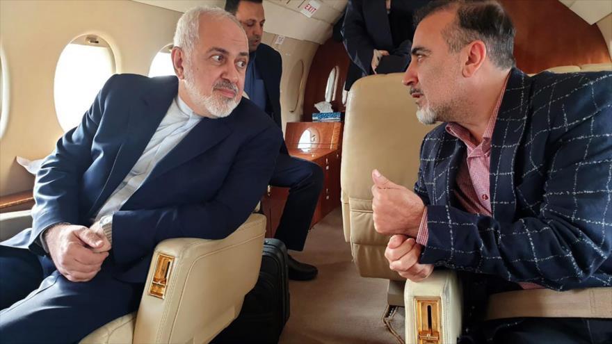 El canciller iraní, Mohamad Yavad Zarif (izda.), y el científico Masud Soleimani en un avión tras su liberación, 7 de diciembre de 2019.