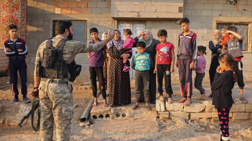 Un soldado proturco habla con residentes de Jan Tamr, al este de la ciudad de Ras al-Ain, Siria, 27 de octubre de 2019. (Foto: AFP)