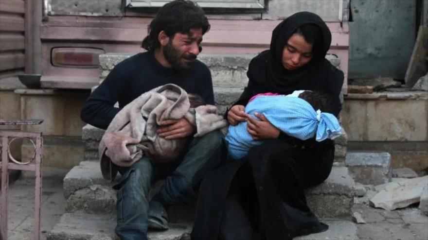 Un hombre y una mujer sirios lloran sosteniendo el cuerpo de uno de sus hijos en la ciudad de Duma, en las afueras de la Damasco, la capital.