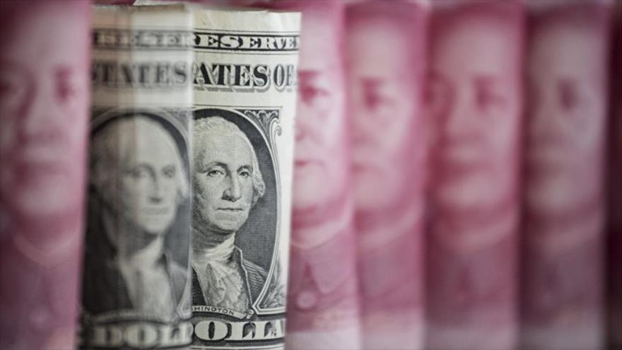 Dos billetes de la divisa de EE.UU. delante de las de China.