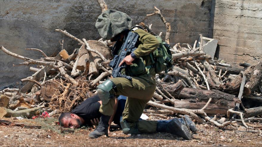 Un soldado israelí detiene a un palestino en una aldea en la Cisjordania ocupada, el 23 de agosto de 2019. (Foto: AFP)