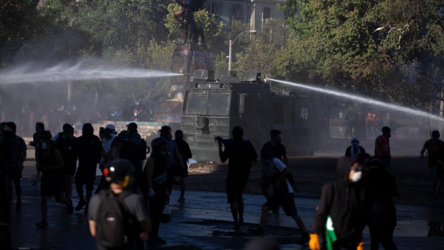 Cañón de agua lanzado contra los manifestantes en una protesta contra el Gobierno del presidente chileno, Sebastián Piñera, Santiago, 27 de diciembre de 2019. (Foto: AFP)