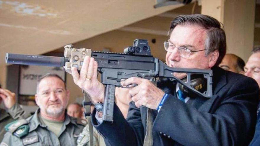 El presidente brasileño, Jair Bolsonaro, apunta con un fusil.