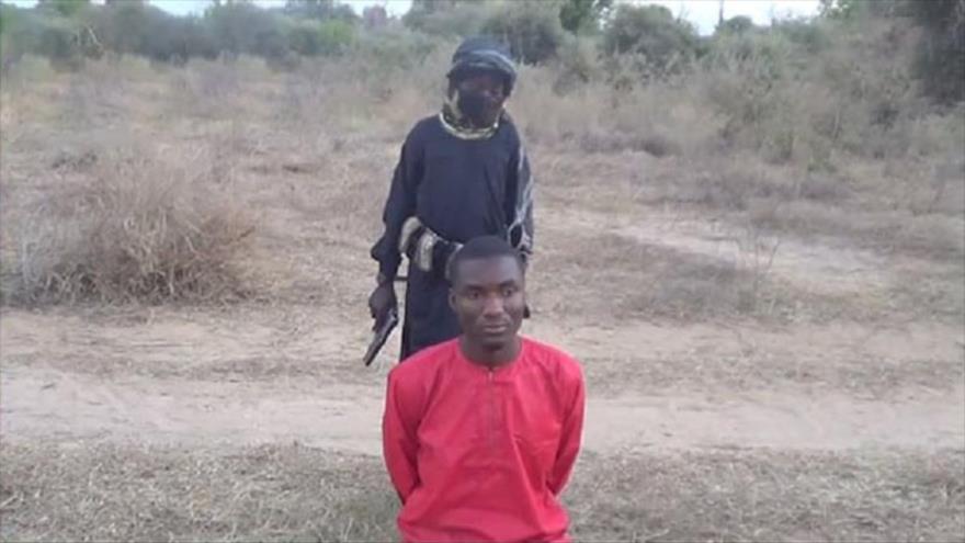 Un niño soldado de Daesh armado con un arma se prepara para asesinar a un preso cristiano en Nigeria.