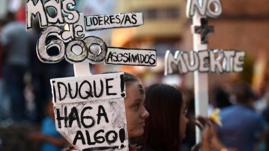 Una mujer sostiene un cartel en una protesta contra el asesinato de líderes sociales en la ciudad de Cali, suroeste de Colombia, 26 de julio de 2019. (Foto: AFP)
