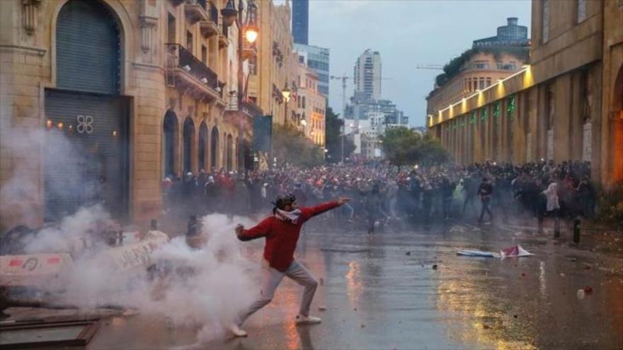 Un manifestante lanza gas lacrimógeno en la protesta junto al Parlamento libanés, 19 de enero de 2020. (Foto: Reuters)