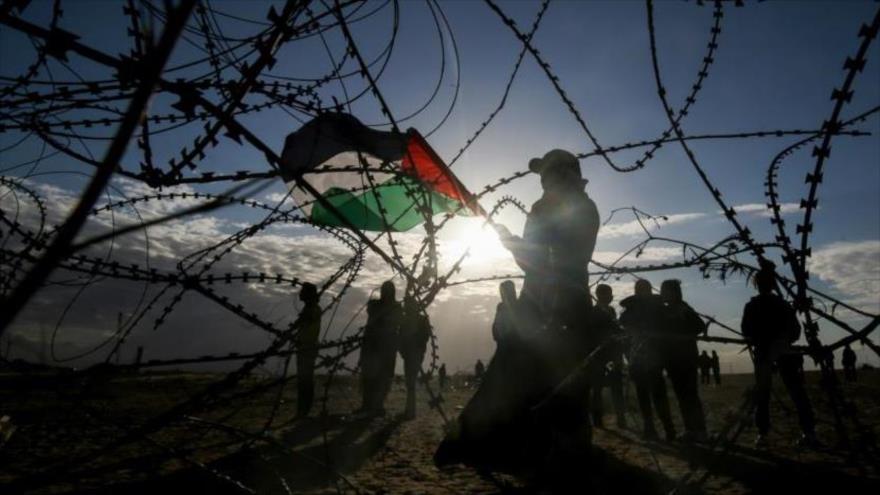 Un palestino lleva una bandera cerca de la línea divisoria entre la Franja de Gaza y los territorios ocupados por Israel.