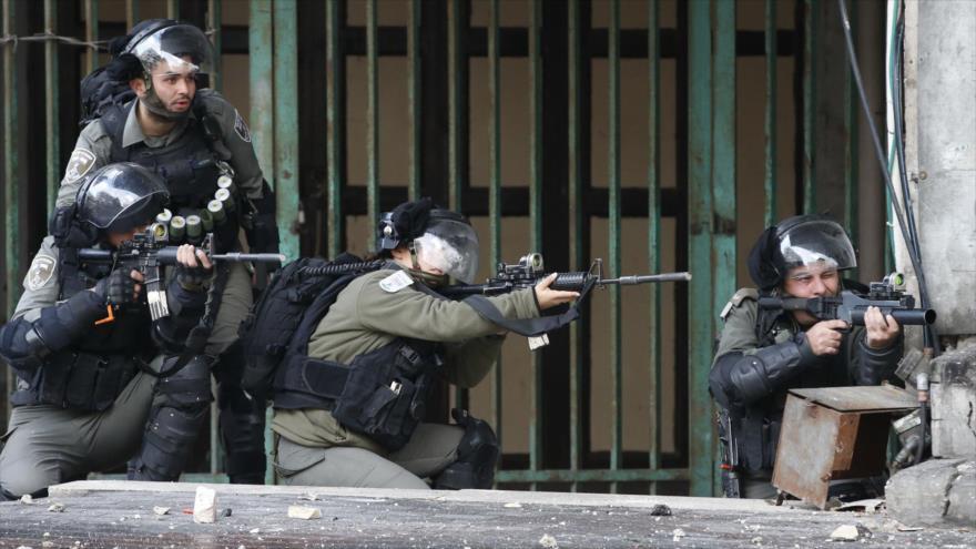 Soldados israelíes apuntan contra manifestantes palestinos en la ciudad de Al-Jalil (Hebrón), en Cisjordania, 9 de diciembre de 2019. (Foto: AFP)