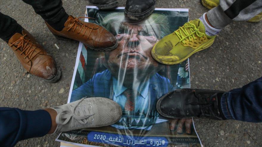Manifestantes pisotean una foto del presidente de EE.UU., Donald Trump, en Bagdad (la capital de Irak), 24 de enero de 2020.