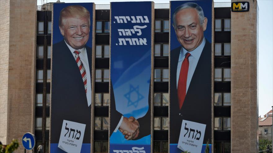 Un gran valla publicitaria muestra al presidente de EE.UU., Donald Trump, y al primer ministro israelí, Benjamín Netanyahu, dándose la mano.