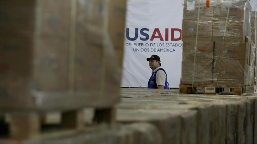 """Un miembro de la Agencia de Estados Unidos para el Desarrollo Internacional (USAID) entre cajas acopiadas en Colombia de la """"ayuda humanitaria"""" destinada a Venezuela."""