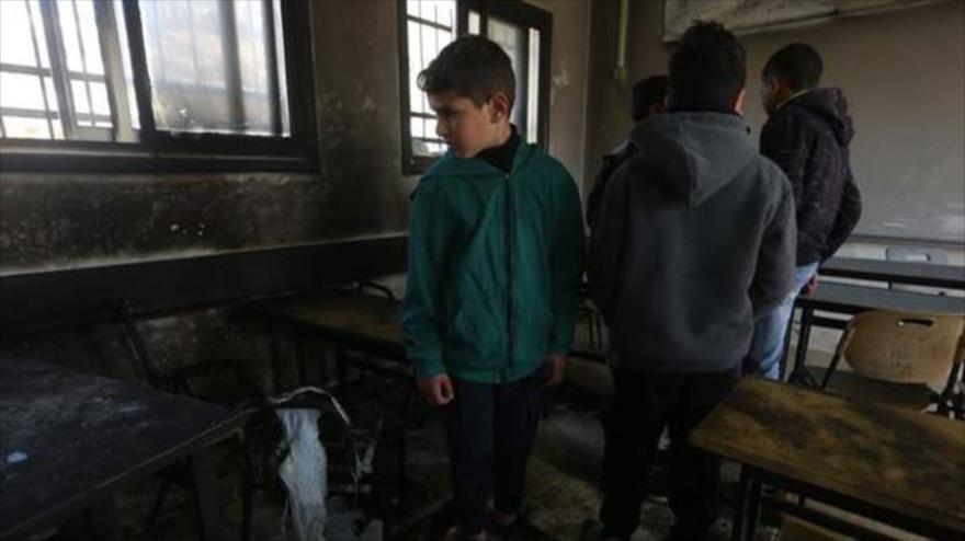 Niños palestinos inspeccionan los daños causados por un incendio provocado por los israelíes en Naplusa, Cisjordania, 28 de enero de 2020.