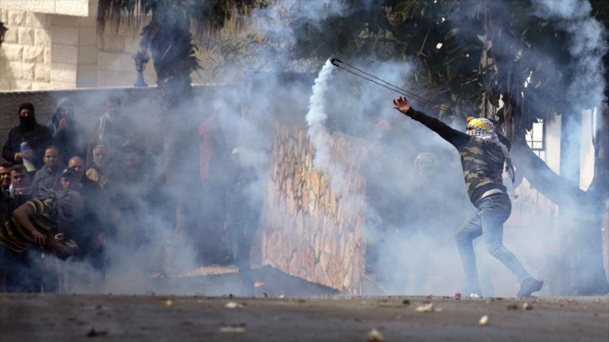 Manifestante palestino arroja gas lacrimógeno hacia las fuerzas israelíes en una localidad cisjordana.