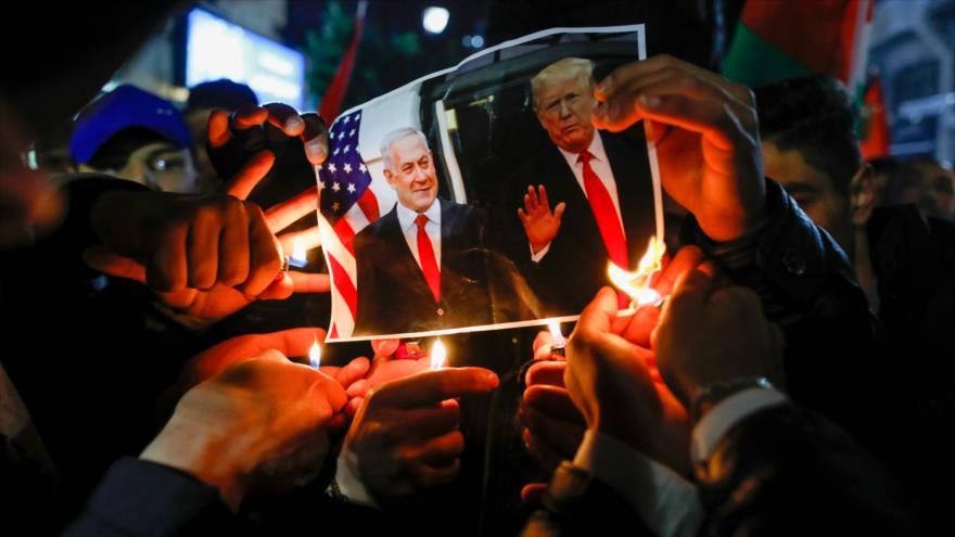 Manifestantes palestinos queman una foto del presidente de EE.UU. y el premier israelí en Ramalá, 28 de enero de 2020. (Foto: AFP)