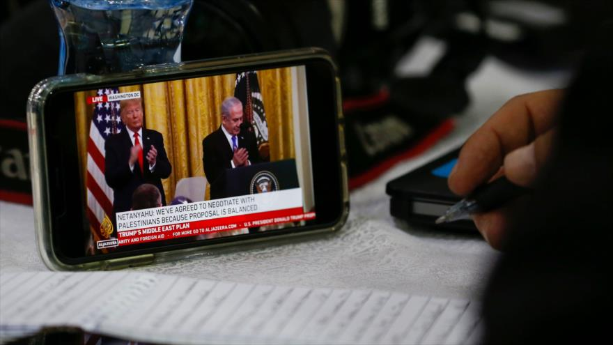 """Un reportero toma nota del contenido del """"acuerdo del siglo"""" propuesto por el presidente de EE.UU., Donald Trump, para poner fin al conflicto israelo-palestino."""