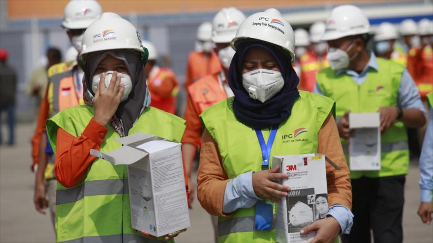 Funcionarios de salud indonesios distribuyen máscaras faciales en el puerto de Panjang en Lampung, Indonesia, 29 de enero de 2020. (Foto: AFP)