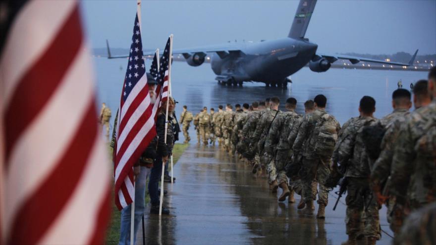 Un regimiento de las fuerzas del Ejército estadounidense se acerca a un avión de transporte para su retirada de alguna base militar de EE.UU. en Irak.