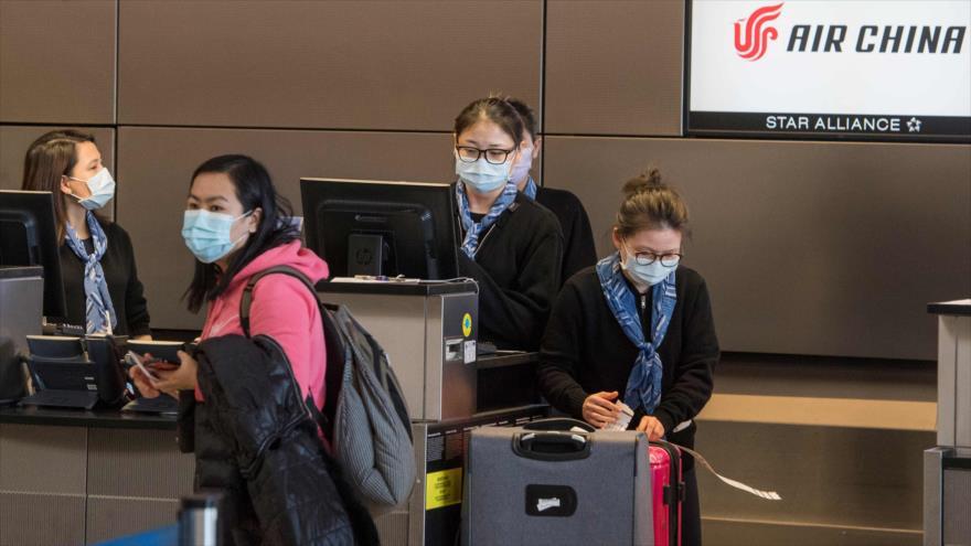 Pasajeros chinos usan mascarillas para protegerse del coronavirus cuando se registran en su vuelo en el aeropuerto de Los Ángeles, 2 de febrero de 2020. (Foto: AFP)