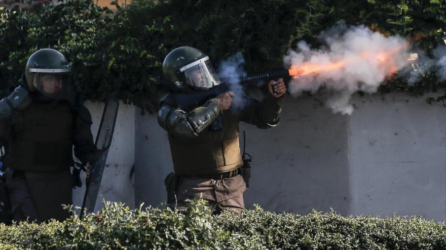 Policía chilena dispara gases lacrimógenos contra la gente durante enfrentamientos en el estadio Nacional de Santiago (capital). 1 de febrero de 2020. (Foto: AFP)