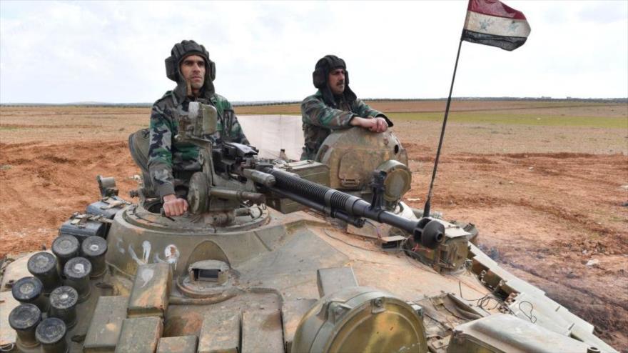 Militares sirios a bordo de un tanque en una localidad en Idlib.