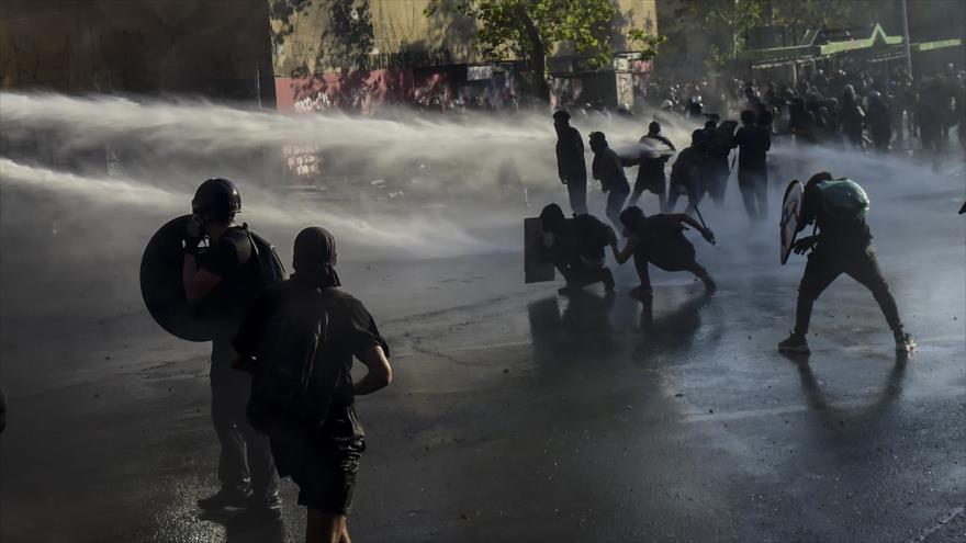 Cañones de agua rocían a manifestantes durante protesta contra el presidente chileno Sebastián Piñera, Santiago, 21 de febrero de 2020. (Foto: AFP)