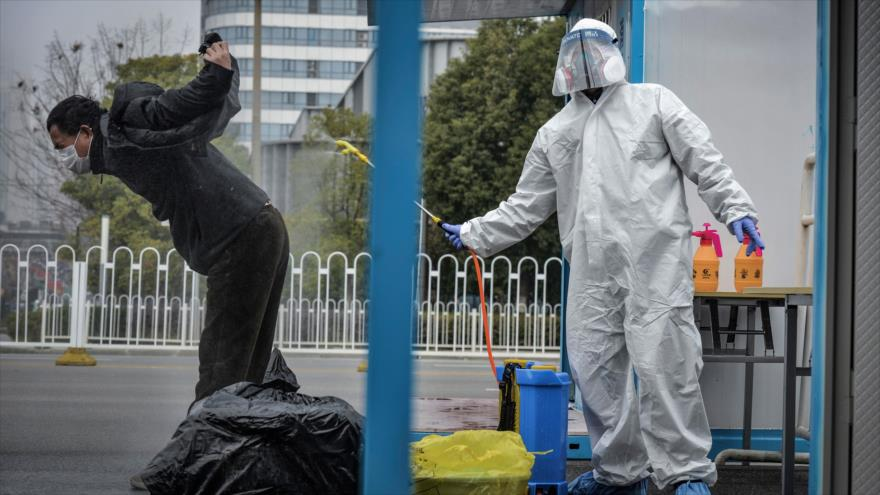 La foto muestra cómo las autoridades sanitarias de China desinfectan a un hombre recuperado de coronavirus, 22 de febrero de 2020. (Foto: AFP)