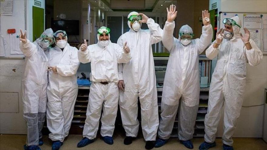 Algunos miembros del sector sanitario de Irán, haciendo gesto de victoria, para mostrar su esperanza para combatir el nuevo coronavirus (COVID-19) en el país.