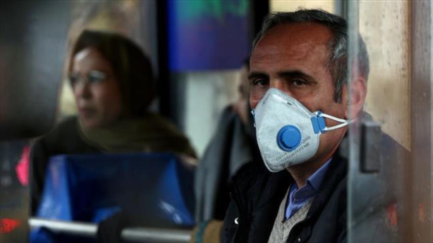 Un hombre iraní usa una mascarilla para evitar contraer el nuevo coronavirus mientras usa un medio de transporte público en Teherán, 25 de febrero de 2020.