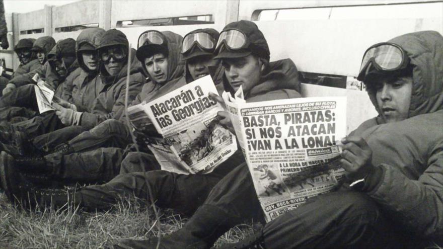 Soldados argentinos leen los periódicos en Puerto Argentino en las Malvinas durante la invasión británica.