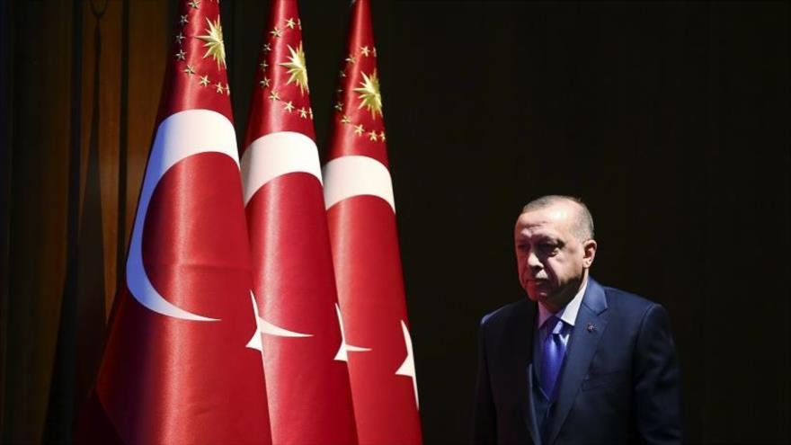 El presidente turco, Recep Tayyip Erdogan, pasa ante una serie de banderas nacionales de Turquía.