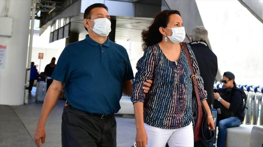 Una pareja usa mascarillas para protegerse contra el COVID-19 en el Aeropuerto Internacional de Los Ángeles, California, 2 de marzo de 2020. (Foto: AFP)