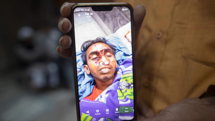 Un pariente muestra la foto de su hijo, Mehtab Ali, asesinato en los episodios de violencia contra los musulmanes en Nueva Delhi, 28 de febrero de 2020. (Foto: AFP)