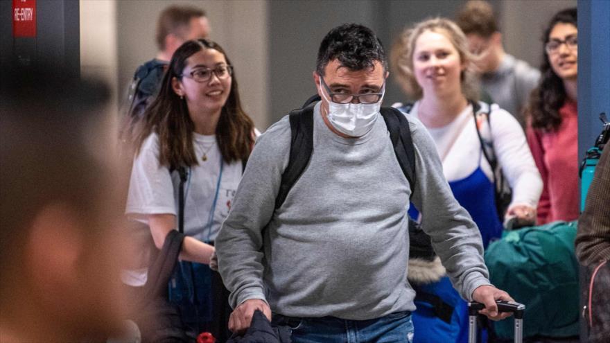 Un pasajero que llega a EE.UU. con una máscara para protegerse de coronavirus, el aeropuerto de Dulles, Washington, el 13 de marzo de 2020. (Foto: AFP)