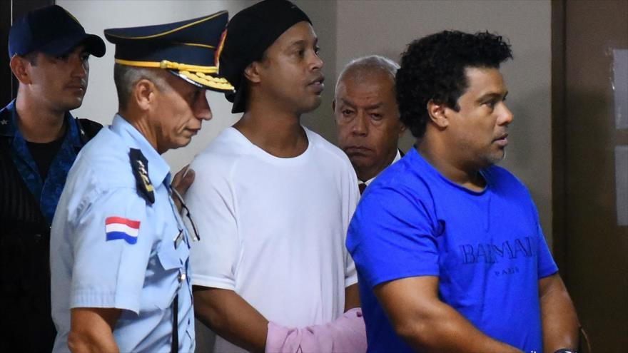 Exfutbolista brasileño Ronaldinho (c) y su hermano llegan al Palacio de Justicia en Paraguay para comparecer ante un fiscal, 7 de marzo de 2020. (Foto: AFP)